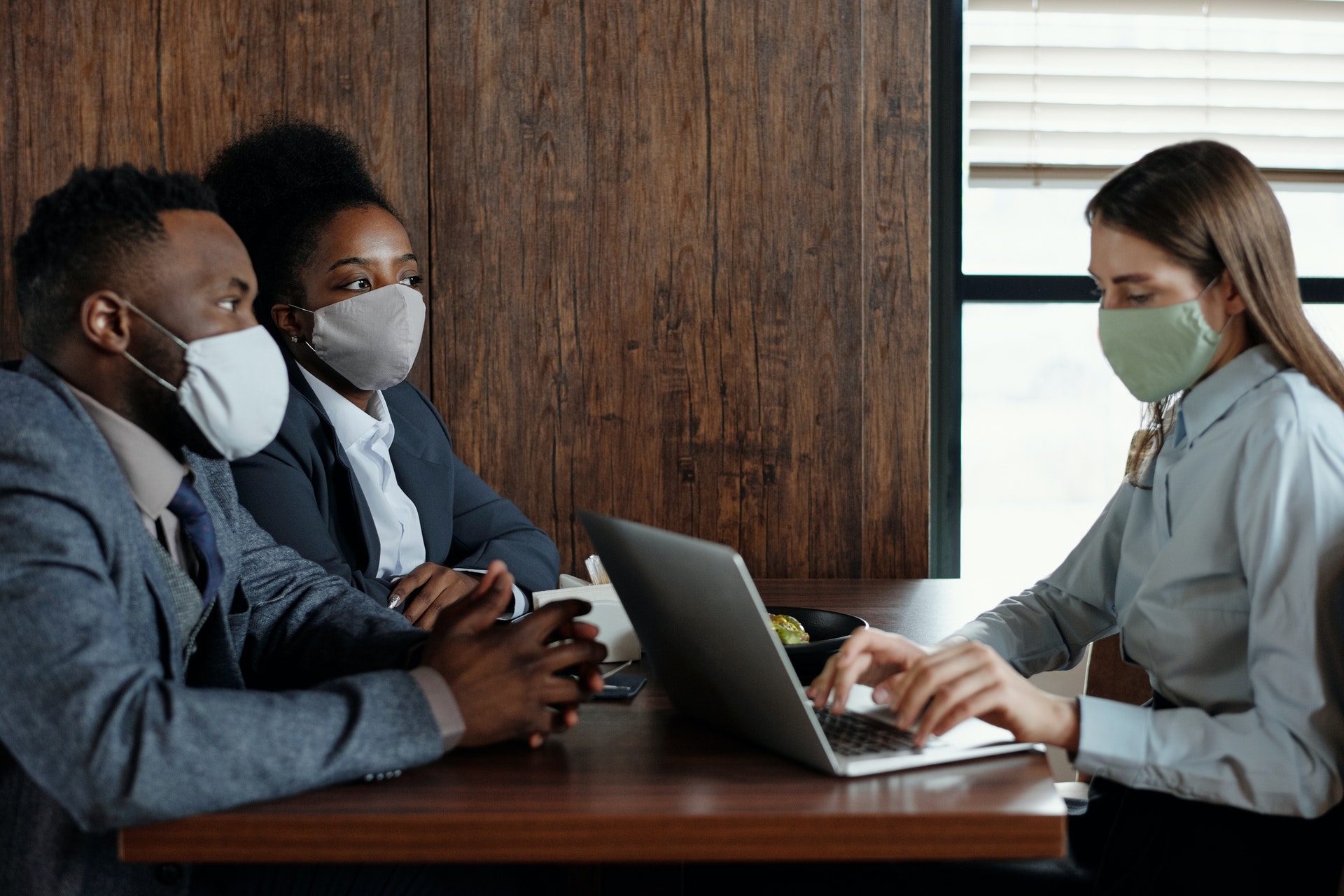 woman at computer with a couple in masks